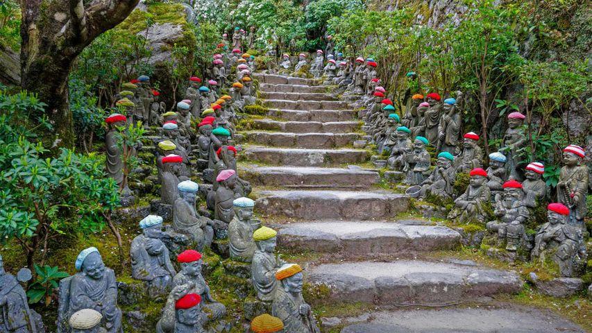 Small rakan statues line the stone pathway to the Daisho-in Temple, Miyajima, Japan